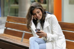 Portrait of beautiful young woman in urban background talking on phone