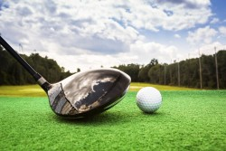 Close-up of a golf ball and a golf wood on a driving range